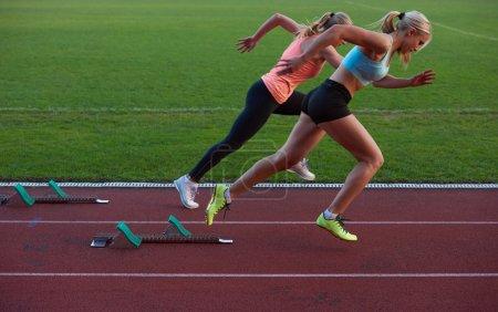 women sprinter leaving starting blocks