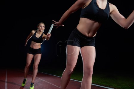 athletic runners passing baton in relay race
