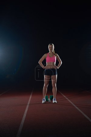 Woman  sprinter at starting blocks