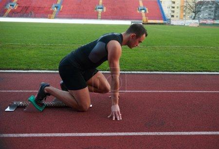 Man sprinter leaving starting blocks