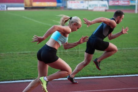 Athletic woman and man on race track