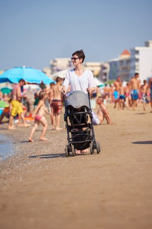 mother walking with baby carriage