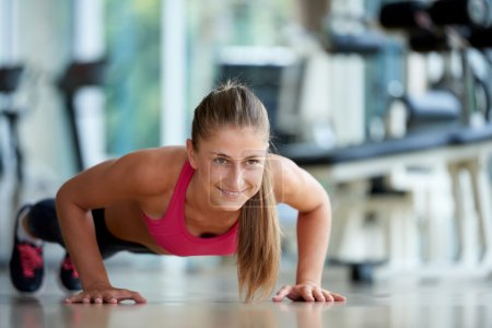 woman doing some push ups at the gym
