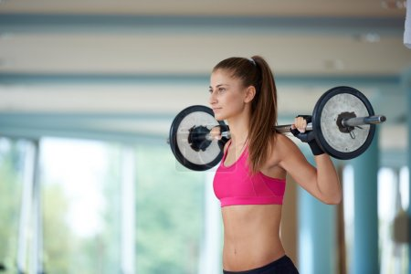 young woman in gym lifting weights