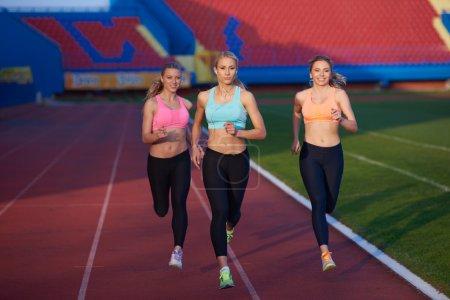 athlete women group  running on athletics race track
