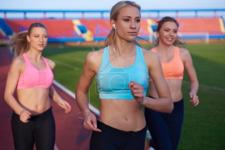 athlete women group  running on athletics race track