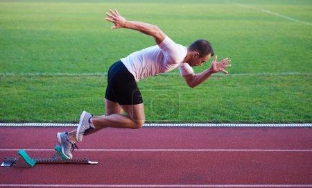 Athletic man start on track