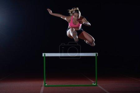 woman athlete and hurdles