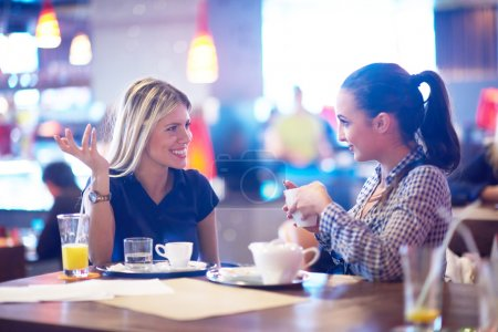 Girls having cup of coffee in restaurant