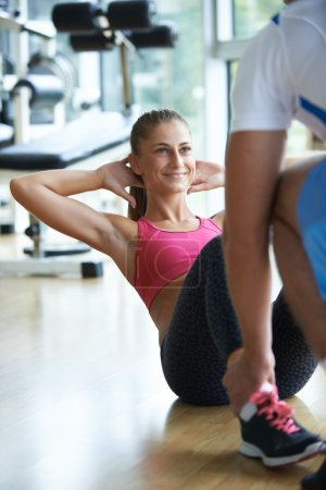 woman with trainer exercise in fitness gym