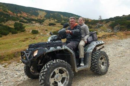 couple driving atv quad bike