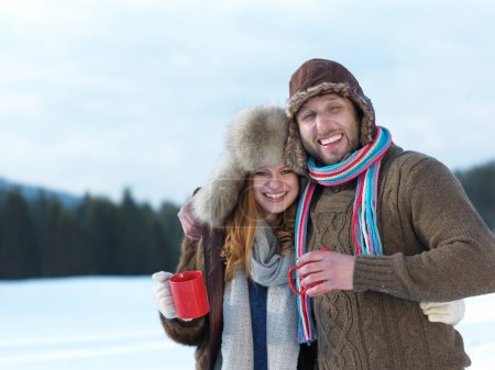 happy young couple drinking warm tea at winter