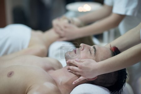 relaxed young couple getting massage in spa