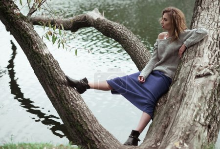 Young beautiful woman posing on a tree.