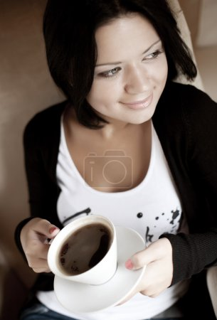 young woman sitting in a cafe drinking coffee