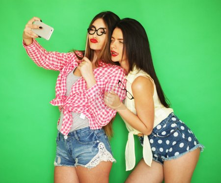 Photo for Two stylish sexy hipster girls best friends ready for party, over green background - Royalty Free Image