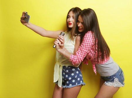 Photo pour Style de vie, bonheur, émotionnel et concept de personnes : deux filles hipster beauté avec un microphone prendre selfie sur fond jaune - image libre de droit