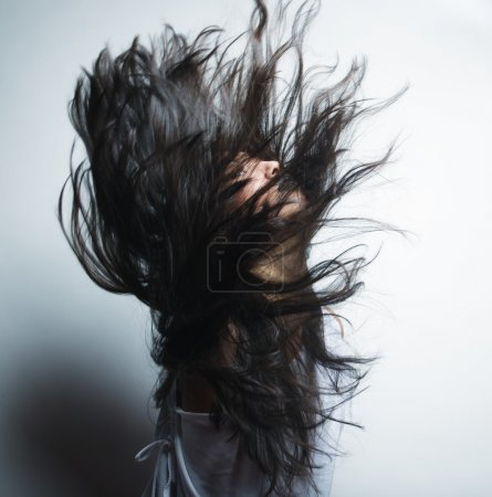 Fashion portrait of a girl with hair lightly fluttering in the w
