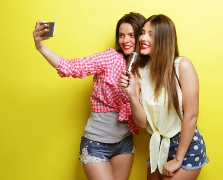 Photo for Life style, happiness, emotional and people concept: two beauty hipster girls with a microphone  take selfie over yellow background - Royalty Free Image