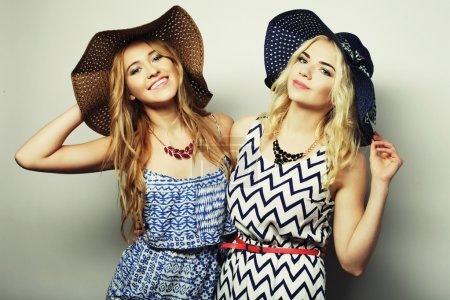 Photo for Fashion concept: two sexy young women in summer fashion dress and straw hats, studio background - Royalty Free Image
