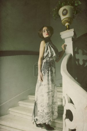 elegant woman in long dress on vintage stairs