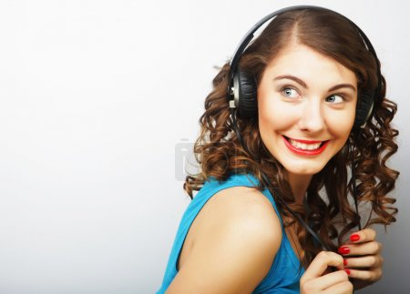 Young curly woman with headphones listening music.