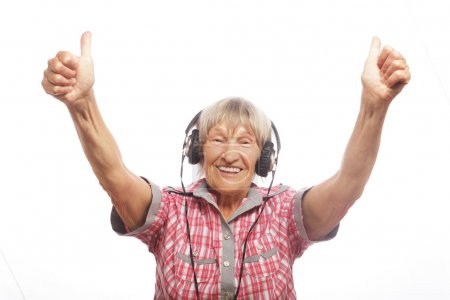 Photo for Funny old lady listening music and showing thumbs up. Isolated on white. - Royalty Free Image