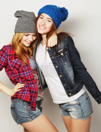 Photo for Fashion portrait of two stylish sexy hipster girls best friends, wearing cute swag outfits and hats. Over gray backround. - Royalty Free Image