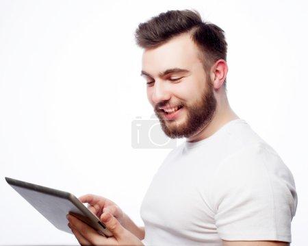 Photo pour Tehnologie et mode de vie concept : jeune homme portant un t-shirt blanc à l'aide d'un ordinateur tablette - isolé sur un fond blanc - image libre de droit