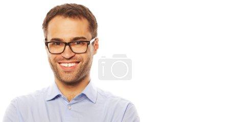 Foto de Negocios, exitosos y personas concepto - hombre de negocios joven guapo en camiseta azul mirando a pie cámara contra fondo blanco - Imagen libre de derechos
