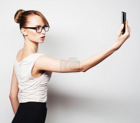 Photo pour Belle jeune femme d'affaires tenant téléphone portable et faisant selfie photo tout en se tenant sur fond gris - image libre de droit