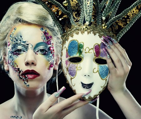 Woman with artistic make-up holding mask