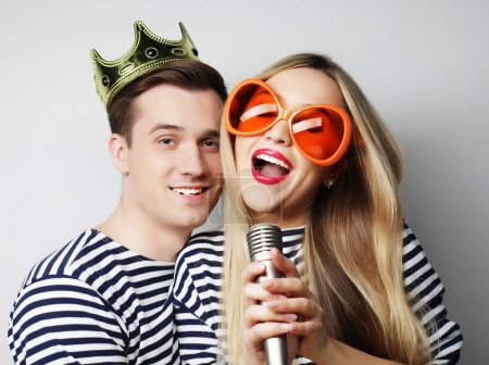 Photo for People, friendship, love and leisure concept - beautiful young loving couple with microphone. Big orange glasses and crown. Ready for party. - Royalty Free Image