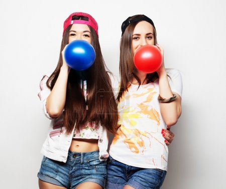 hipster girls smiling and holding colored balloons