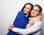 lovely happy couple hugging over grey background.