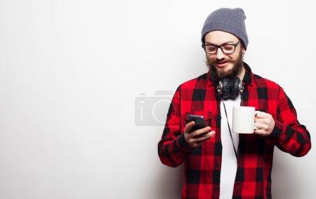 Photo pour Style de vie, bonheur et concept de personnes : jeune homme barbu avec téléphone portable à la main sur fond gris . - image libre de droit