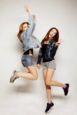 Foto de Retrato de estilo de vida de dos jóvenes hipster chicas mejores amigos saltar sobre fondo gris - Imagen libre de derechos