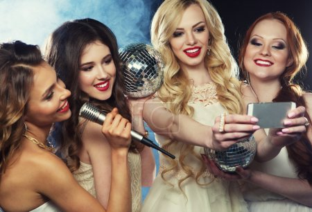 Four beautiful stylish girls singing karaoke