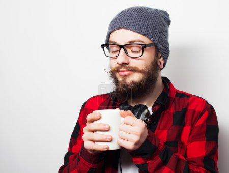Photo pour Concept de vivres, de bonheur et de personnes : jeunes barbus homme avec une tasse de café sur fond gris - image libre de droit