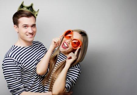 Foto de Concepto personas, amistad, amor y ocio - hermosa joven amante pareja con micrófono. grandes cristales naranjas y corona. listo para la fiesta. - Imagen libre de derechos