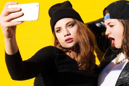 Photo pour Deux amies adolescentes en tenue de hipster à l'extérieur faire selfie sur un téléphone. - image libre de droit