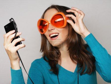 Photo pour Jeune femme heureuse avec un casque d'écoute de musique sur fond blanc - image libre de droit