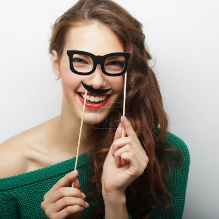 Attractive playful young woman holding mustache and glasses on a