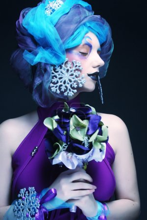 woman with creative make up holding a bouquet of jewelry