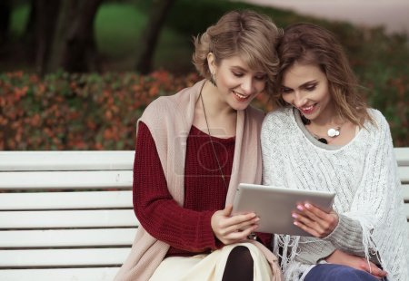beautiful women girls autumn using tablet outdoor