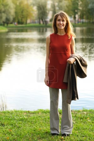 Photo for Beautiful elegant woman standing in a park in autumn - Royalty Free Image