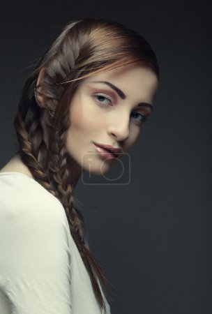 portrait of beautiful young blonde woman with creative braids ha