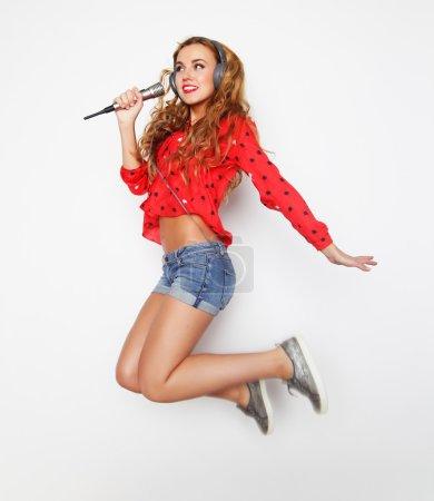 Photo pour Femme heureuse avec microphone sautant et chantant - image libre de droit