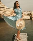 Young happy woman posing near sea