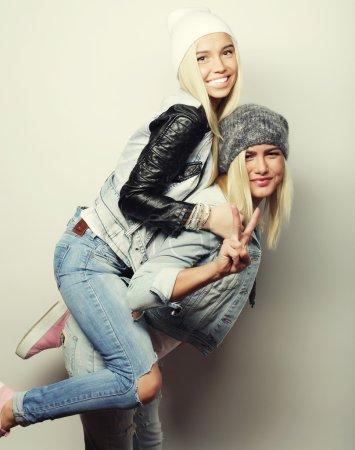 Photo pour Émotionnel, style de vie, le bonheur et les gens concept : Happy girl piggybackking avec petite amie. Studio tourné sur fond blanc - image libre de droit